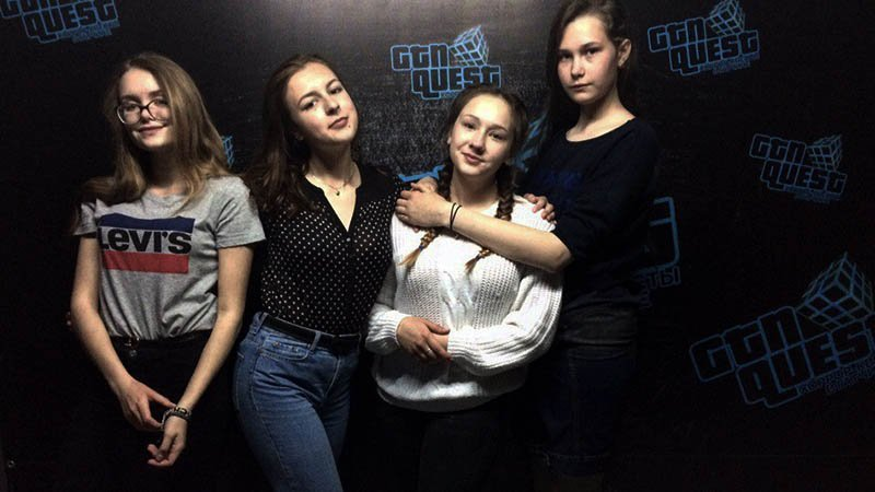 Four girls pose in front of the camera after finishing an escape quest.