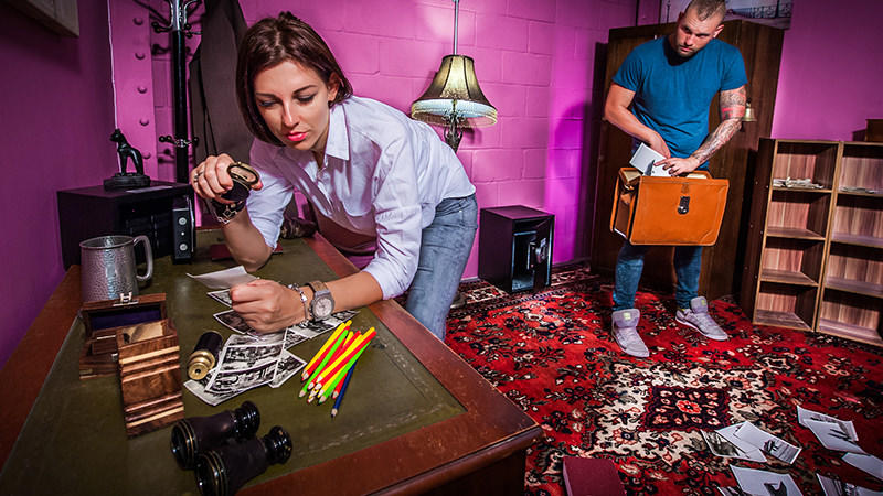 Man searches through a case with documents, lady examines photos in a detective escape room.