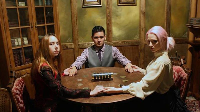 Three people forming a hand circle around the table in an escape room.