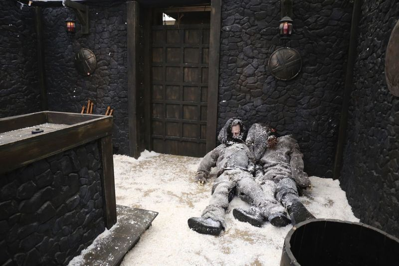 Well-decorated extreme escape room with an imitation of snow and two corpses lying around.