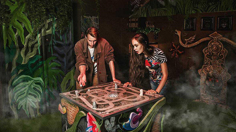 Two people play a tabletop game during a jungle escape quest.