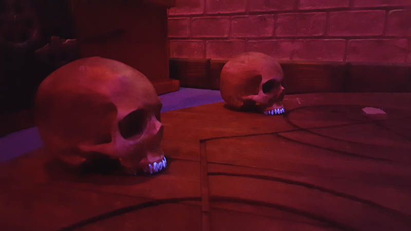 There are old human skulls on the floor. Perform a dark magic ritual with them, and you'll unlock the exit.