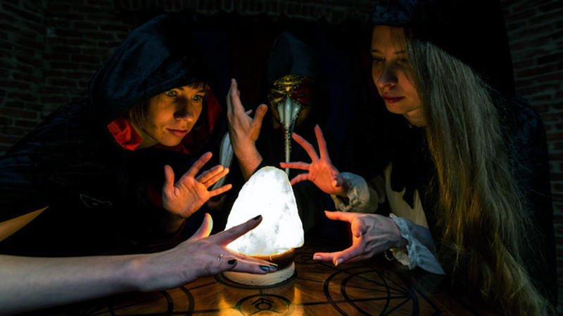 Two young ladies try to figure out the right solution to the magical puzzle in a mystical escape room. They are dressed in black robes, so they need to think like witches to progress further.